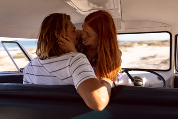 Young couple kissing each other in front seat of camper van at beach