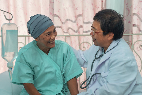 asian female cancer patient with headscraf look happy talk with doctor after chemotherapy