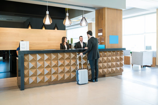 Happy Hotel Clerks Are Welcoming Professional At Counter
