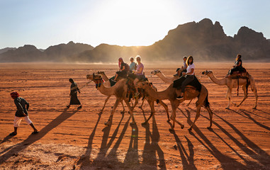 Photo sur Plexiglas Maroc Women riding through the desert in Wadi Rum, Jordan, on camels lead by Bedouin guides.