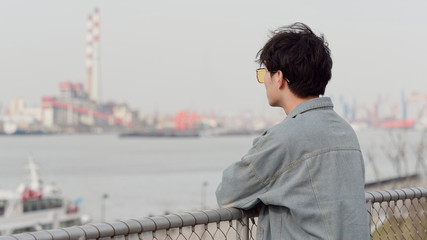 Portrait of a handsome Chinese young man standing and looking away with arms leaning on rail in windy sunny day, facing the Huangpu river in Shanghai, rear view.