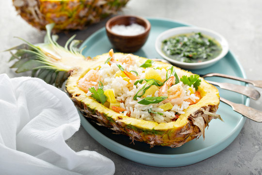 Shrimp rice with green onions served in pineapple boats