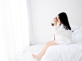 Happy Asian woman using vintage camera and sits on bed in the morning at home.