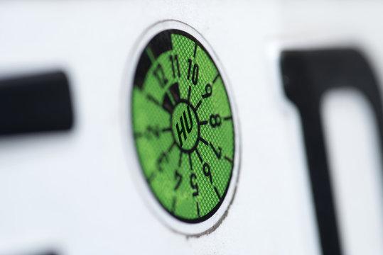 Eine Tüv Plakette am Kennzeichen