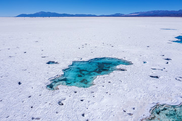 Drone point of view of an emerald lake in the desert of Salinas Grandes, one of the most spectacular landscape on earth. Long extension of white snowy salt in the desert in Jujuy province, northern Ar