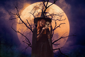 Halloween witch holding a skull standing over dead tree, full moon and spooky cloudy sky, Halloween mystery concept