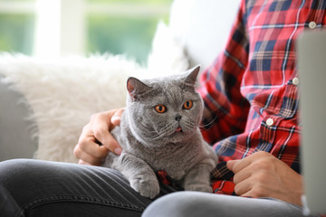 Young man with cute cat at home