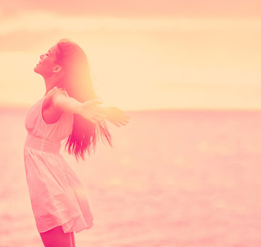 Well-being woman stress free feeling happy emotion with open arms on sunset nature background. Wellness happiness in life.