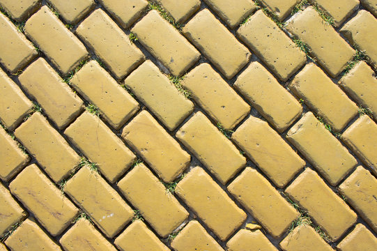 Yellow brick road sprouted by green grass under the bright summer sun