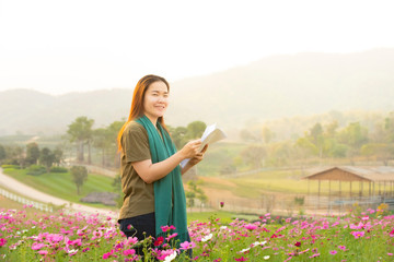 Asian woman in casual dress standing in cosmos flower field hand hold set of paper look at camera,student university college do research of vegetation. Wall mural