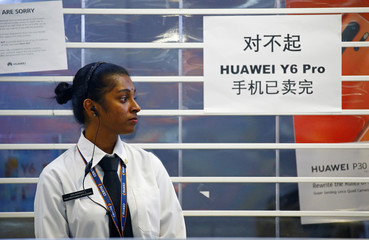 A security officer stands outside a closed Huawei store with a sold-out sign in Singapore