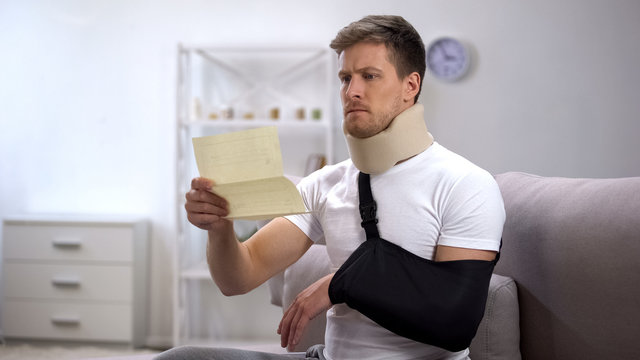 Man in foam cervical collar and arm sling reading medical bill, shocking price