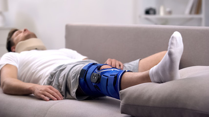 Male in foam cervical collar and neoprene knee brace sleeping on sofa, recovery