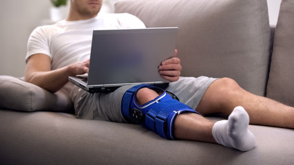 Man in arthritis knee brace working on laptop at home rehab period and freelance