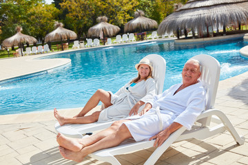 Senior couple relaxing by the swimming pool