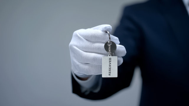 Reserved word on keychain in receptionist hand, luxury property rental in resort