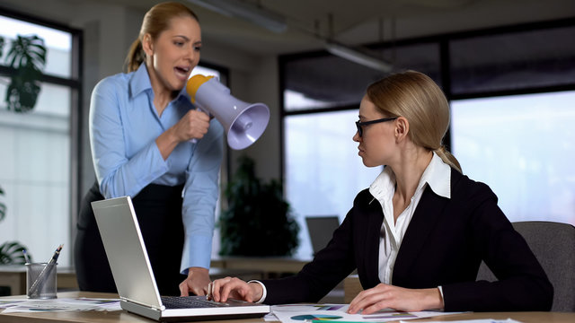 Lady boss shouting with megaphone at colleague, authoritarian leadership