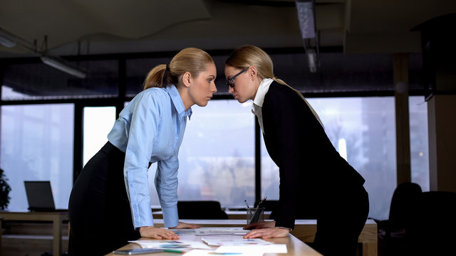 Two businesswomen looking with challenge at each other, competition at work
