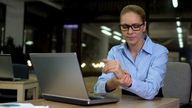 Woman feels wrist pain caused by excessive use of laptop, carpal tunnel syndrome