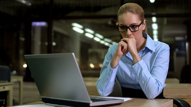 Nervous business woman looking at laptop, afraid of work failure and bad news