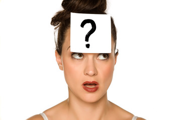 a young confused woman with a drawn question mark on paper on a white background