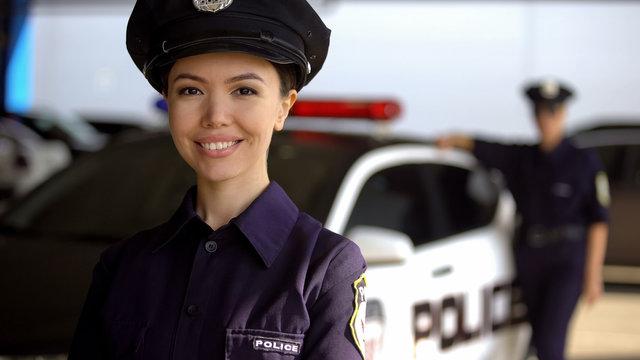 Smiling asian policewoman posing to camera against partner near patrol car, duty