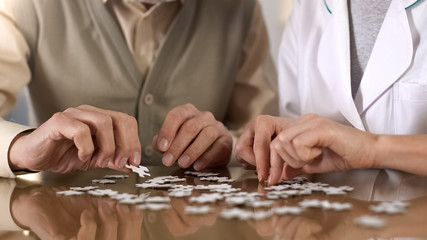 Female caregiver helping aged man doing puzzle table, mental training, alzheimer Wall mural