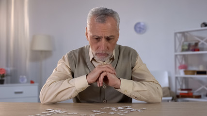 Old man exercises with puzzle, suffers cognitive impairment, Alzheimer symptom Wall mural