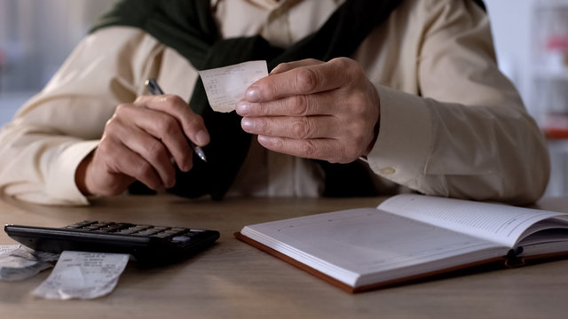 Pensioner looking at checks, calculating expenses for utilities and purchases