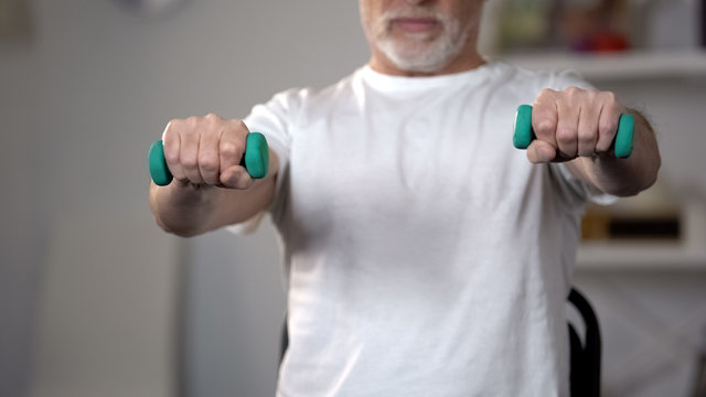 Old man lifting dumbbells, training muscles and joints after injury or insult