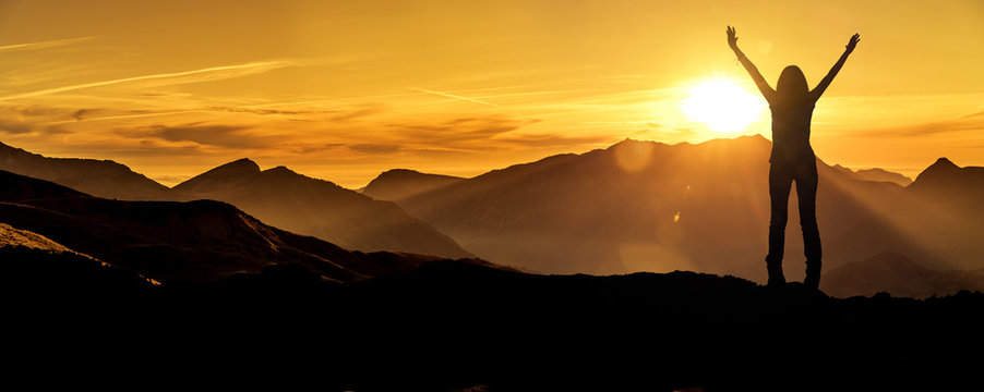 Frau in Siegerpose bei Sonnenaufgang auf einem Berggipfel