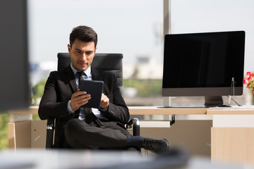 Businessman sitting and using  tablet computer..