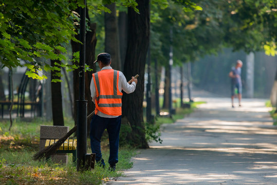 Cleaning leaves in the city, janitor sweeping the foliage in city park. A street sweeper with broom, work of housing and communal services