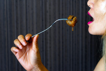 Asian female holding fork eating meatball with sweet chilli sauce