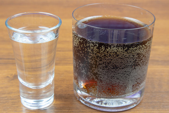 Vodka and cola in different glasses on a wooden table