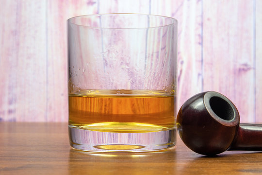 A glass of whiskey and a smoking pipe on a wooden table