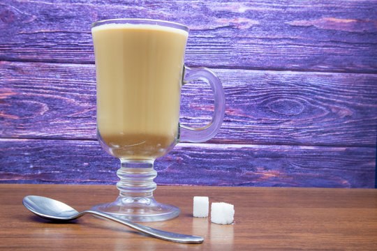Latte coffee in a tall glass on a wooden table