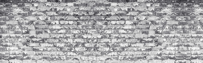 Wide light gray shabby brick wall texture. Old masonry with peeling white paint. Weathered...