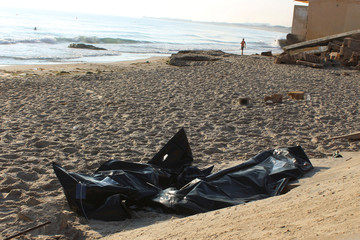 Bags containing the bodies of migrants who died after their wooden boat capsized off the coast of Komas, are seen in the town east of the capital Tripoli