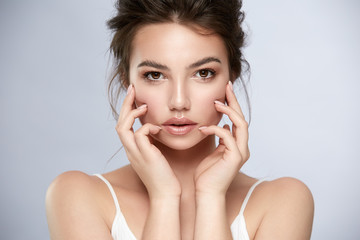 strong woman face with perfect nude make-up and big lips isolated on grey