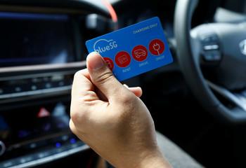 Musician Peter Huang shows his BlueSG charging membership card while driving his Hyundai Ioniq Electric car in Singapore