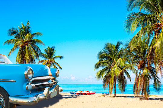 The tropical beach of Varadero in Cuba with american classic car, sailboats and palm trees on a summer day with turquoise water. Vacation background.