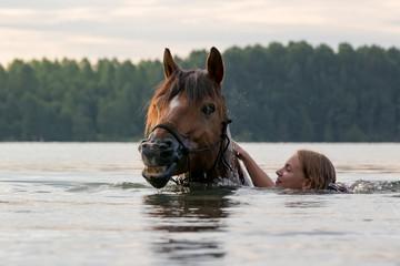 Mädchen badet mit Pferd im See