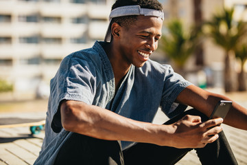 Skateboarder smiling with a mobile phone
