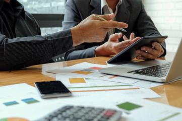 Management team work on tablet to summarize work to achieve organizational goals.
