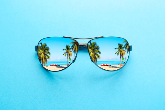 Summer vacation concept. Sunglasses with ocean beach and palms on blue background.