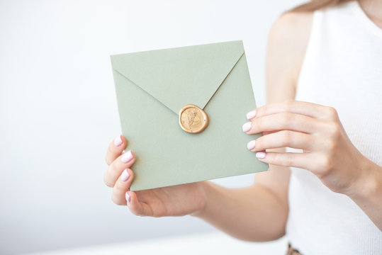 Close-up photo of female hands holding invitation envelope with a wax seal, a gift certificate, a postcard, wedding invitation card