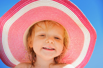 A cute little girl in a big straw hat at the sea