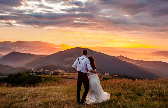 couple in love, a guy and a girl in wedding clothes are standing in the mountains and looking at the sunrise, a beautiful sunrise of the sun in the mountains