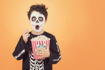 Happy Halloween.Surprised child in a skeleton costume with popcorn Wall mural